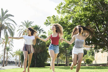 Spain, Mallorca, Palma, three happy young running holding hands together in a park in summer - IGGF00487