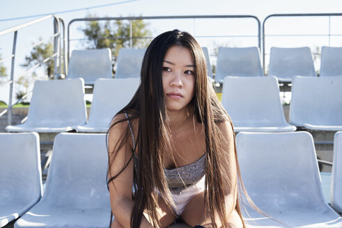 Portrait of  young woman sitting on grandstand of a stadium - IGGF00490