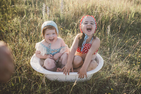 Two girls in field, playing in plastic tub of water - ISF01391