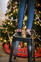 Child on stool reaching up to decorate Christmas tree - ISF01400