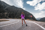Young woman standing on mountain road with hairpin bend, Draja, Vaslui, Romania, rear view - ISF01403