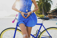 Neck down view of young woman with bicycle making heart shape with hands on sandy beach, Krabi, Thailand - ISF01418