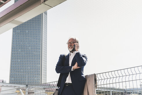 Smiling mature businessman in the city on cell phone - UUF13652
