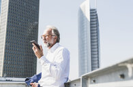 Mature businessman in the city using cell phone - UUF13664