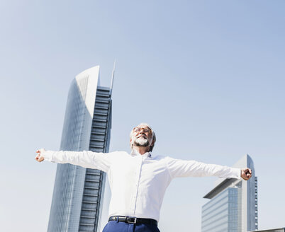 Happy mature businessman cheering in the city - UUF13667