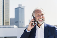 Smiling mature businessman in the city on cell phone - UUF13670