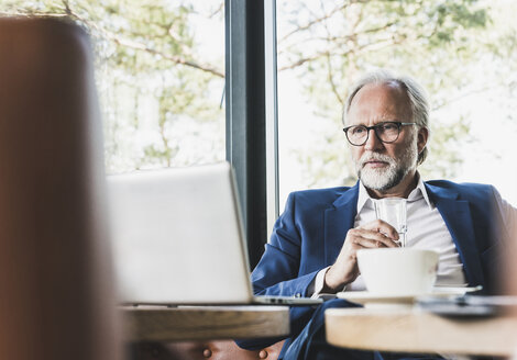Mature businessman sitting at table in a cafe using laptop - UUF13676