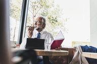 Mature businessman working at table in a cafe - UUF13682