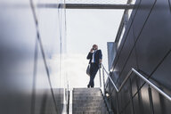 Smiling mature businessman at staircase in the city on cell phone - UUF13685