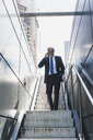 Smiling mature businessman on staircase in the city on cell phone - UUF13688