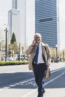 Smiling mature businessman in the city on cell phone on the go - UUF13694