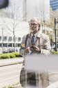 Mature businessman with cell phone and takeaway coffee in the city - UUF13697