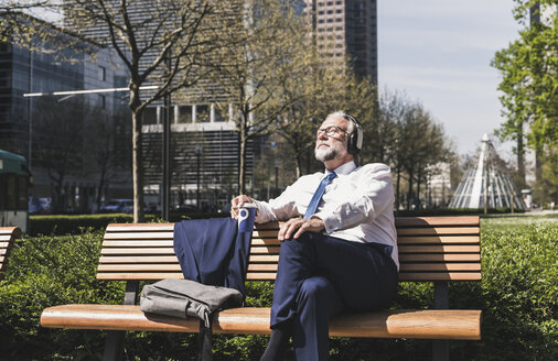 Mature businessman sitting on a bench listening to music - UUF13700