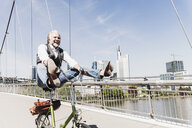 Playful mature man on bicycle on bridge in the city - UUF13706