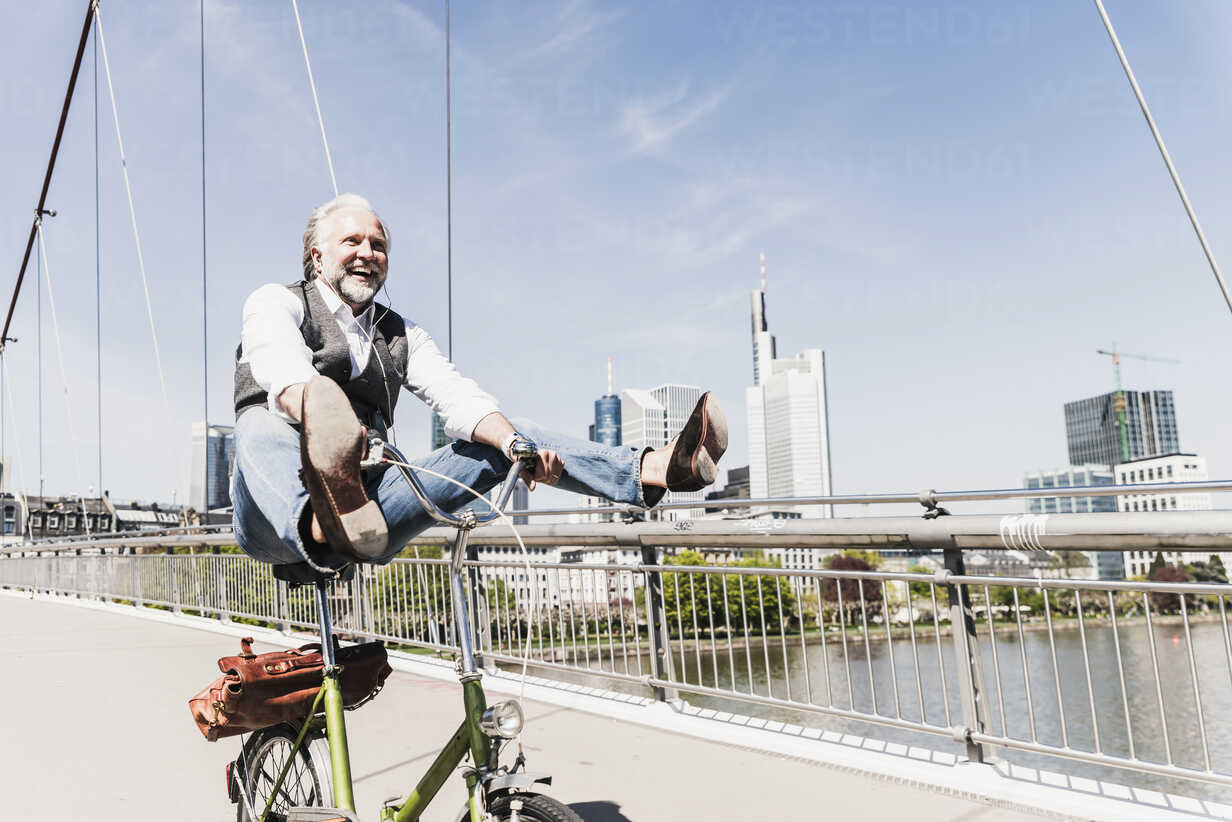 Playful mature man on bicycle on bridge in the city - UUF13706 - Uwe Umstätter/Westend61