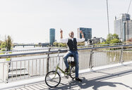 Happy mature man with bicycle listening to music on bridge in the city - UUF13709