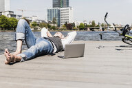 Mature man with laptop and earbuds lying at the riverside in the city - UUF13712