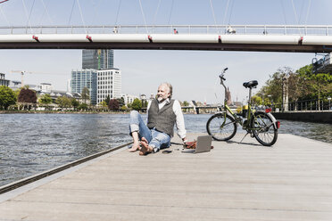 Smiling mature man with laptop and bicycle sitting at the riverside in the city - UUF13715