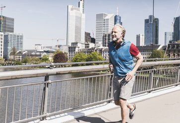 Smiling mature man with headphones running on bridge in the city - UUF13718