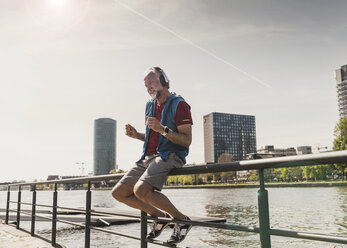 Happy athletic mature man with headphones sitting at the riverside in the city - UUF13724