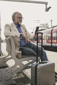 Mature businessman sitting at train station with cell phone, earbuds and suitcase - UUF13730