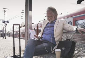 Mature businessman sitting at train station with cell phone, earbuds and notebook - UUF13733