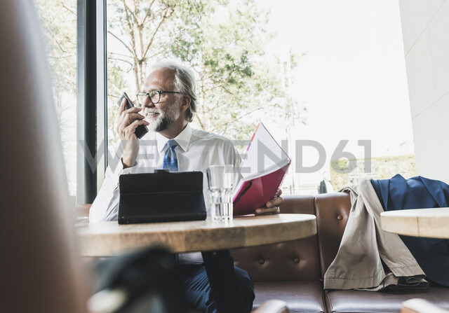Smiling mature businessman working at table in a cafe - UUF13736