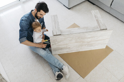 Father and daughter assembling a wooden table at home - JRFF01647