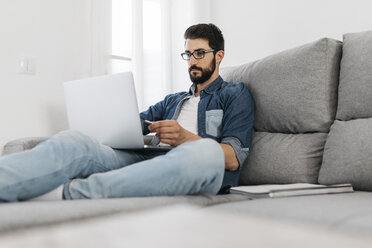 Man using laptop, working on the couch at home - JRFF01662