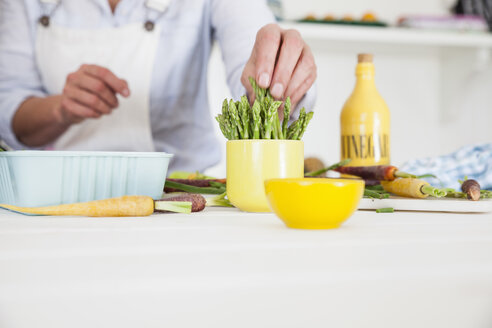 Mid section of woman preparing asparagus at kitchen table - CUF05732