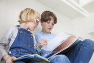 Girl reading storybook with brother on kitchen counter - CUF05768