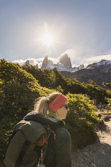 Female hiker hiking near sunlit  Fitz Roy mountain range in Los Glaciares National Park, Patagonia, Argentina - CUF05894