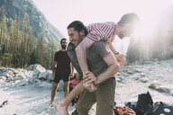 Young man carrying friend over shoulder on riverside, Lombardy, Italy - CUF05900
