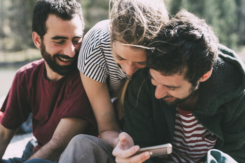 Three young adult friends looking and laughing at smartphone, Lombardy, Italy - CUF05903