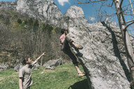 Young male boulderer pointing for woman climbing boulder, Lombardy, Italy - CUF05909