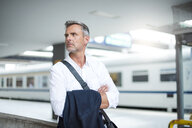 Mature businessman looking over his shoulder from train station platform - CUF05930
