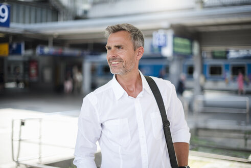 Smiling mature businessman in train station - CUF05933