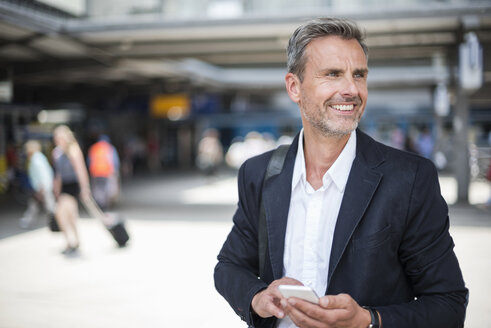 Smiling mature businessman with smartphone in train station - CUF05936