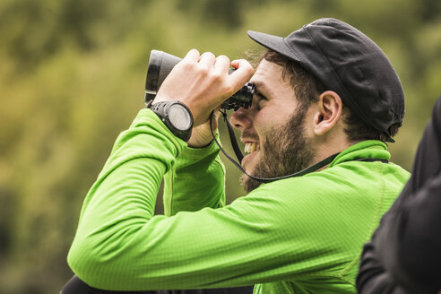Young male backpacker looking through binoculars in Queulat National Park, Chile - CUF05954