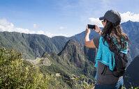 Woman takes a picture on her smartphone of Machu Picchu on the Inca Trail, Cusco, Peru - CUF05957