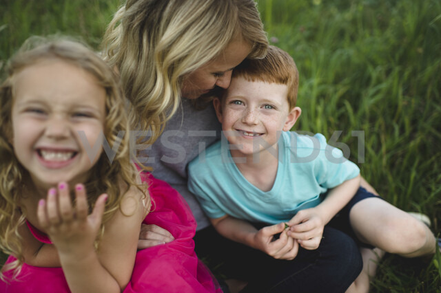 Portrait of girl and brother sitting on mothers lap in grass - CUF05963