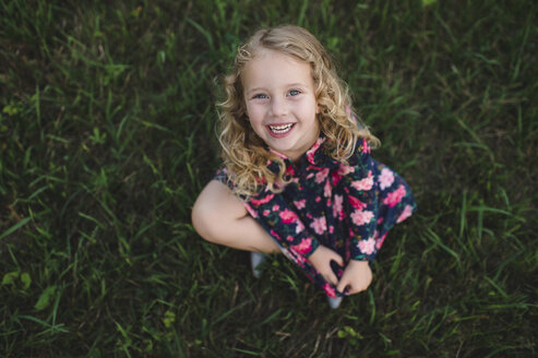 Overhead portrait of blond haired girl sitting on grass - CUF05966