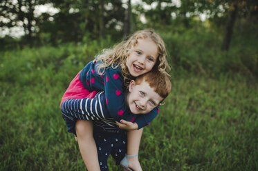 Portrait of boy giving sister a piggyback in field - CUF05969