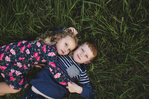 Overhead portrait of boy and sister lying on grass hugging - CUF05972