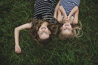 Overhead upside down portrait of girl and her sister lying on grass - CUF05981