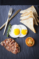 Overhead view of toast with bacon, fried eggs and tomato breakfast on slate - CUF06326