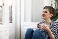 Happy woman sitting relaxed at window, drinking coffee - FKF02888