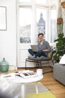 Woman sitting in chair at home, using laptop - FKF02891