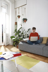Woman sitting on couch, using laptop - FKF02912