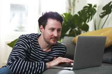 Man sitting at home, using laptop - FKF02915